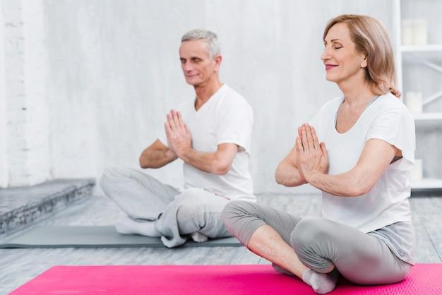 Pareja feliz haciendo meditación en estera de yoga Foto gratis