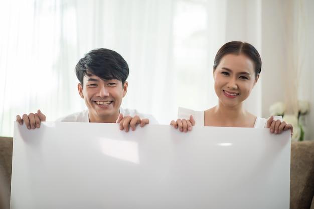 Pareja feliz mano sosteniendo el espacio en blanco blanco Foto gratis