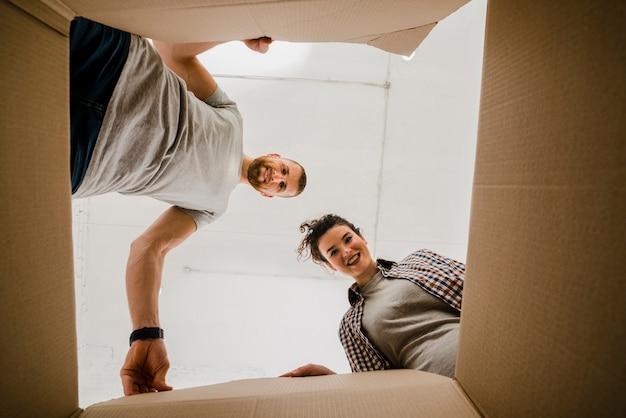 Pareja feliz mirando dentro de la caja Foto gratis