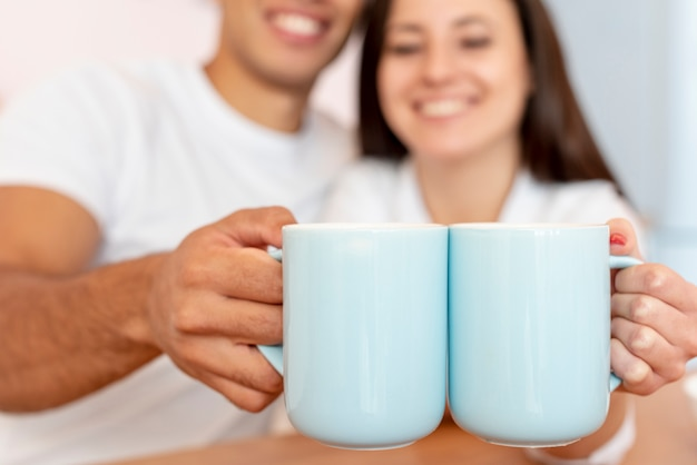 Pareja feliz de primer plano con tazas azules Foto gratis
