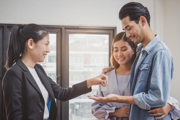 Pareja feliz recibiendo la llave del apartamento del agente de bienes raíces Foto Premium
