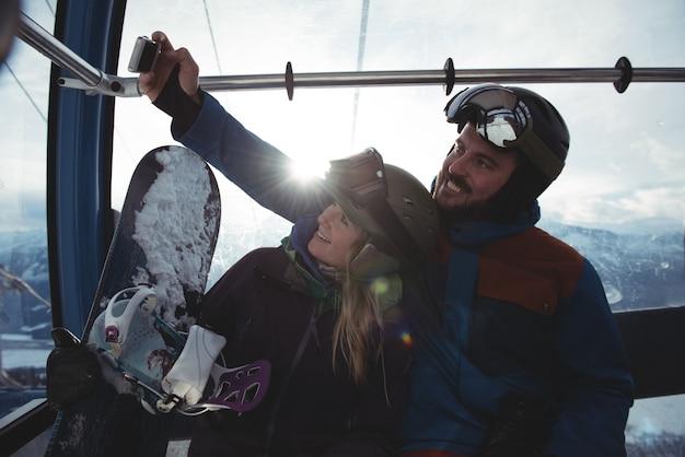 Pareja feliz teniendo selfie en teleférico contra el cielo Foto gratis