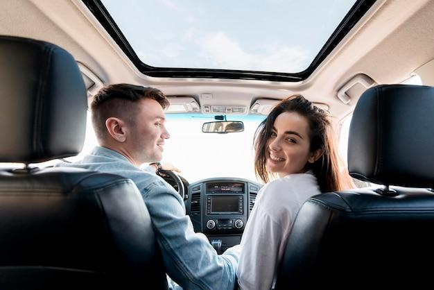 Pareja feliz de tiro medio en coche Foto Premium