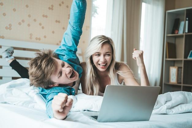 Pareja feliz usando la computadora portátil en la cama Foto gratis