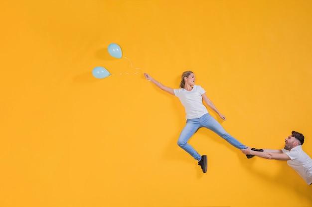 Pareja flotando en el aire con globos Foto gratis