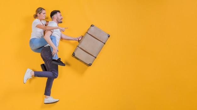 Pareja flotando con un maletín Foto gratis