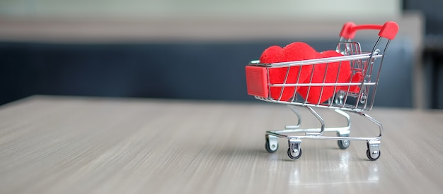 Pareja de forma de corazón rojo en mini carro de compras en la mesa de madera. concepto de amor y compras. Foto Premium