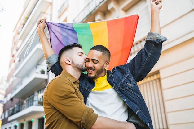 Pareja gay abrazando y mostrando su amor con la bandera del arco iris. Foto Premium