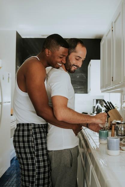 Pareja gay abrazándose en la cocina Foto Premium