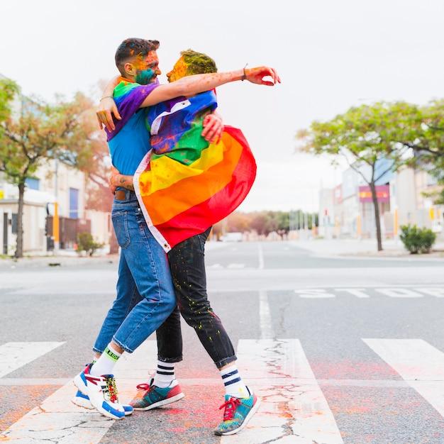 Pareja gay alegre abrazando envuelto en banderas de arco iris en el camino Foto gratis
