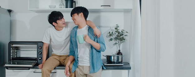 Pareja gay asiática tomando café, pasando un buen rato en casa. los jóvenes y guapos hombres lgbtq + que hablan felices se relajan descansan juntos y pasan un momento romántico en la moderna cocina de la casa por la mañana. Foto gratis