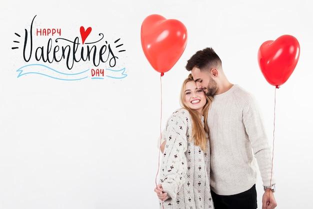 Pareja con globos de corazón en el día de san valentín Foto gratis