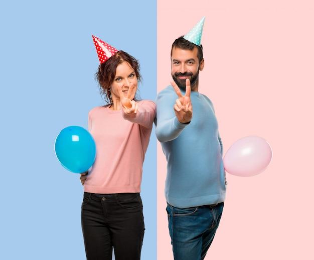 Pareja con globos y sombreros de cumpleaños sonriendo y mostrando el signo  de la victoria  d35cd836a44