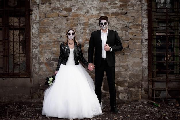 Pareja de halloween vestido con ropa de boda zombie romántico Foto Premium