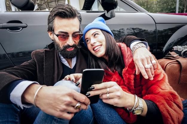 Pareja hipster divirtiéndose con teléfono móvil inteligente en coche roadtrip Foto Premium