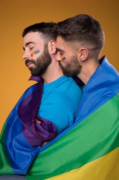 Pareja de homosexuales abrazando amorosamente envuelta en una bandera de arco iris Foto gratis