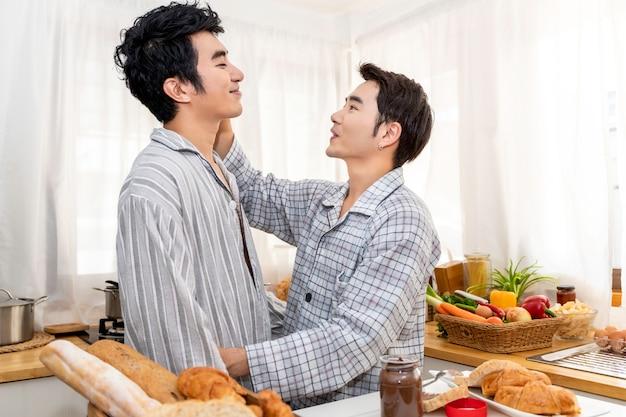 Pareja de homosexuales asiáticos cocinar el desayuno en la cocina en la mañana Foto Premium