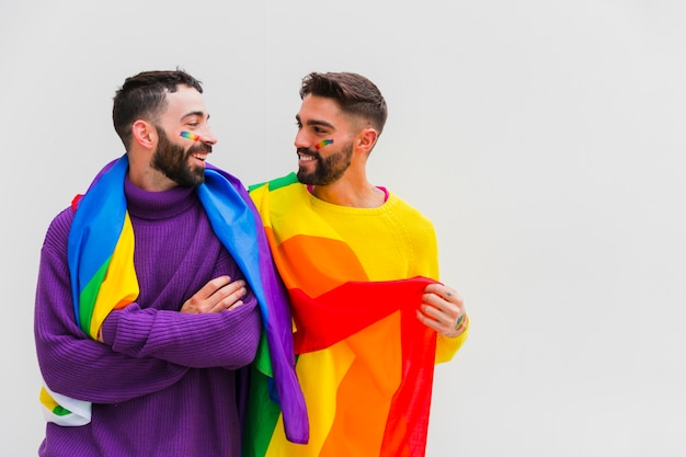 Pareja de homosexuales con banderas lgbt en los hombros sonriendo juntos Foto gratis