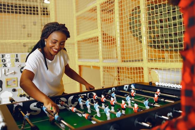 Pareja internacional jugando un futbolín en un club Foto gratis