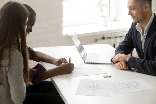 Pareja interracial firma contrato de inversión de hipoteca en reunión con corredor Foto gratis