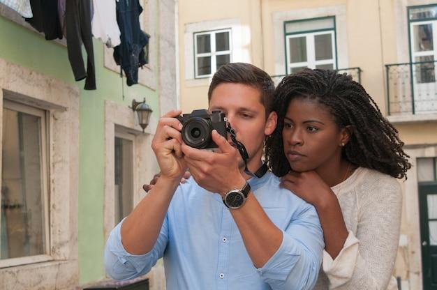 Pareja interracial seria tomar fotos en la cámara en la ciudad Foto gratis