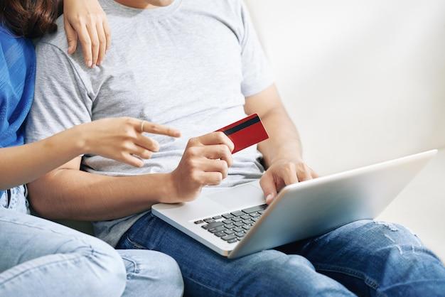 Pareja irreconocible sentado en el sofá con laptop y hombre con tarjeta de crédito Foto gratis