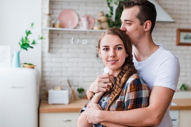 Pareja joven abrazando y besando en la cocina Foto gratis
