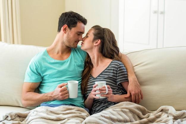 Pareja joven abrazándose en el sofá mientras toma un café en la sala de estar Foto Premium