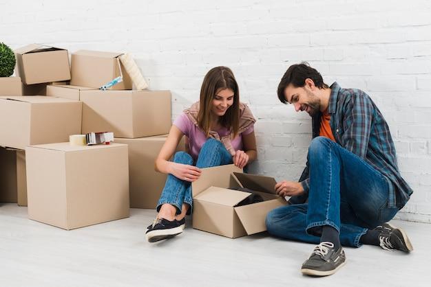 Pareja joven abriendo las cajas de cartón en su nueva casa. Foto gratis