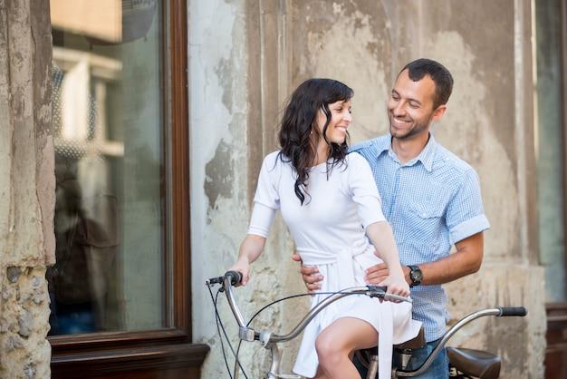 Pareja joven en bicicleta tándem retro en la calle de la ciudad Foto Premium