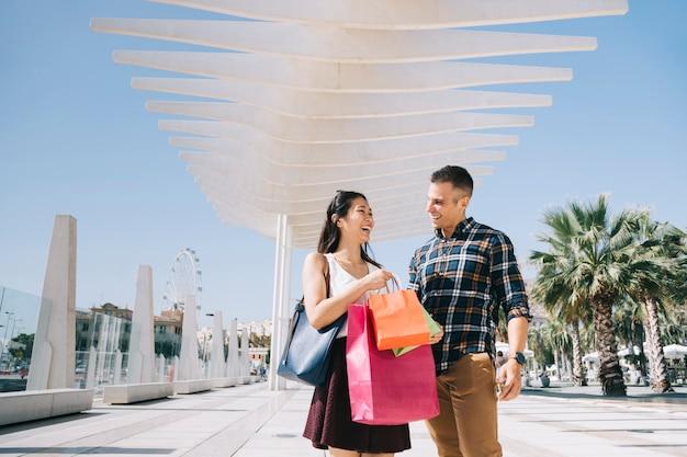 Pareja joven con bolsas andando afuera Foto gratis