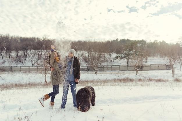 Pareja joven caminando con un perro en un día de invierno Foto gratis