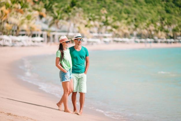 Pareja joven caminando en una playa tropical con arena blanca y agua turquesa del océano en la isla de antigua en el caribe Foto Premium