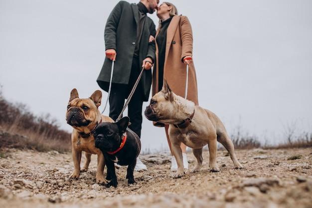Pareja joven caminando sus bulldogs franceses en el parque Foto gratis