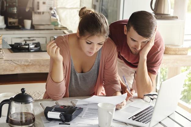 Pareja joven casada con muchas deudas haciendo papeleo juntos, revisando sus facturas, planificando el presupuesto familiar y calculando las finanzas en la mesa de la cocina con papeles Foto gratis