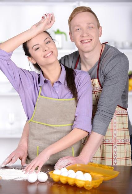 Pareja joven cocinando en la cocina de sus casas. Foto Premium