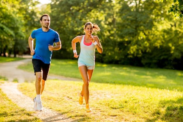 Pareja joven corriendo en el parque en un día soleado | Foto Premium