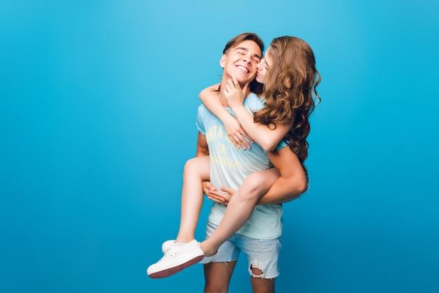Pareja joven divirtiéndose sobre fondo azul en estudio. chica guapa con pelo largo y rizado está montando en la espalda del chico guapo. ella lo está besando. Foto gratis
