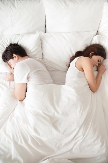 Pareja joven durmiendo por separado en la cama, espalda con espalda, vertical. Foto gratis