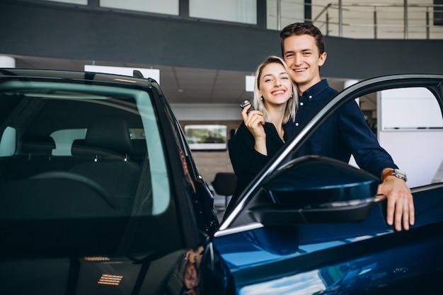 Pareja joven eligiendo un automóvil en una sala de exhibición de autos Foto gratis