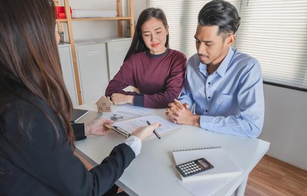 Pareja joven de la familia escucha al agente de bienes raíces explicar sobre el contrato de compraventa Foto Premium