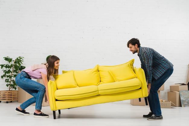 Pareja joven feliz colocando el sofá amarillo en la sala de estar Foto gratis