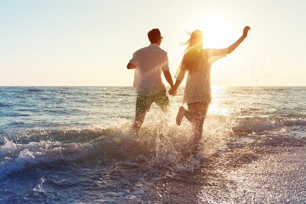 Pareja joven feliz disfrutando del mar Foto Premium