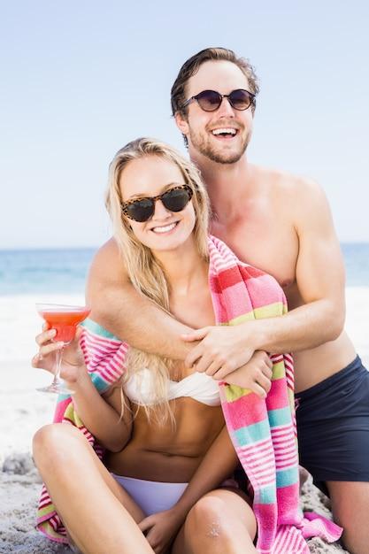 Pareja joven en gafas de sol abrazando en la playa Foto Premium