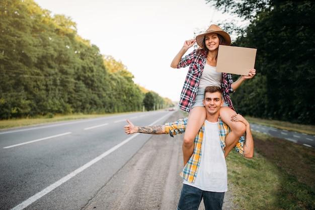 Pareja joven haciendo autostop con cartón vacío. aventura de autostop de hombre y mujer. autostopistas felices en la carretera Foto Premium