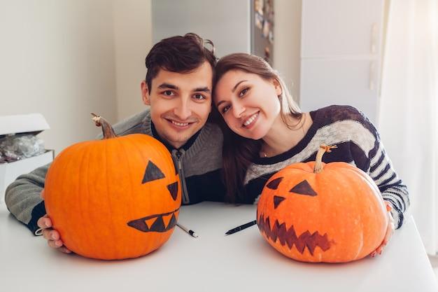 Pareja joven haciendo jack-o-lantern para halloween en la cocina. feliz hombre y mujer prepararon calabazas para vacaciones Foto Premium