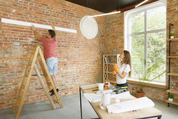 Pareja joven haciendo reparación de apartamentos juntos ellos mismos. hombre y mujer casados haciendo remodelación o renovación de la casa Foto gratis