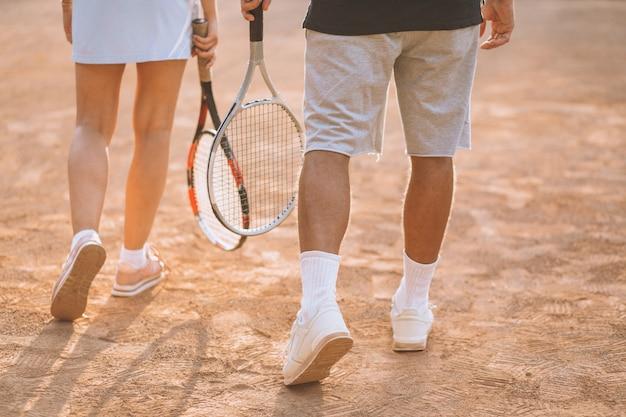 Pareja joven jugando al tenis en la cancha, pies de cerca Foto gratis