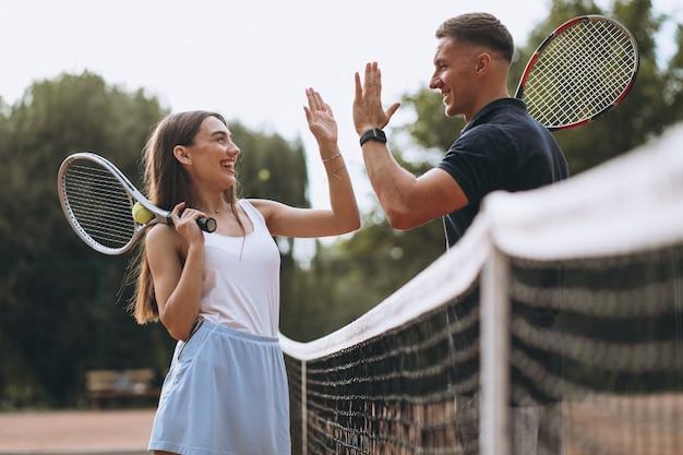 Pareja joven jugando tenis en la cancha Foto gratis