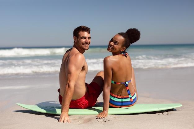 Pareja joven mirando a la cámara mientras está sentado en la tabla de surf en la playa bajo el sol Foto gratis
